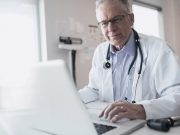 Doctor working at laptop in clinic office